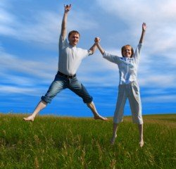 Healthy couple jumping in field